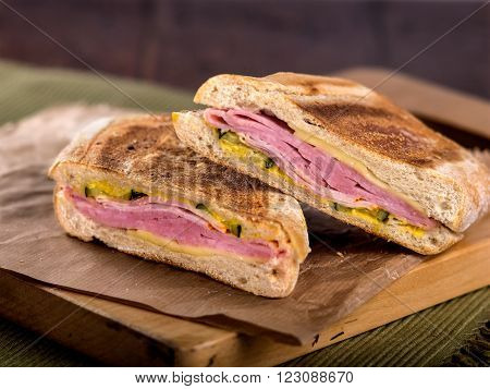 Ham and cheese toasted panini sandwich on wooden cutting board