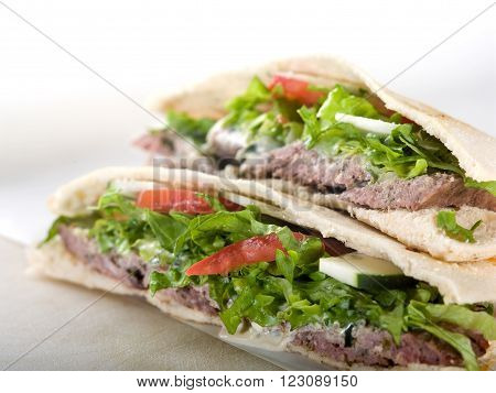 Gyro pita bread sandwich on white cutting board