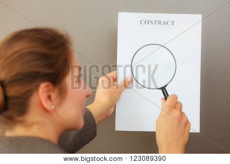 Contracts and agreements concept. Rear view of adult woman in jacket holding showing contract. Close up portrait of person with loupe studying agreement.