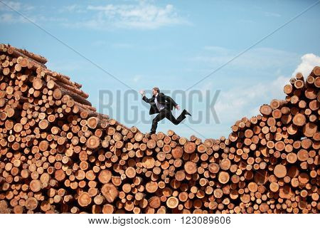 Metaphor - running business Man on his way to the  top of large pile of logs -