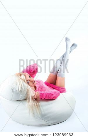 Portrait of a sexy young woman sitting on pouf in studio background.