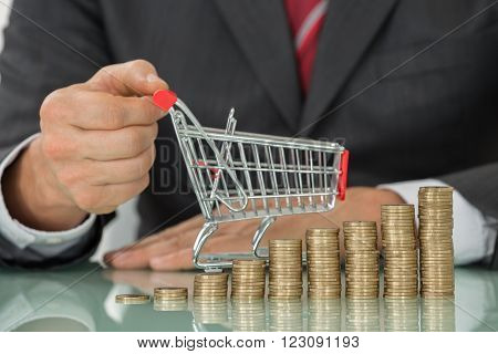 Businessman With Stack Of Coins And Shopping Cart
