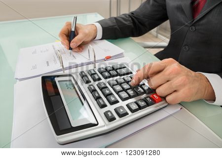 Close-up Of Businessman Calculating Invoice Using Calculator