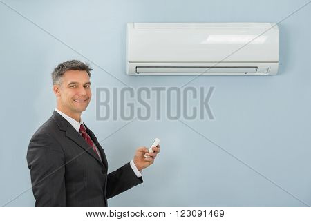 Mature Happy Businessman Holding Remote Control Air Conditioner In Office