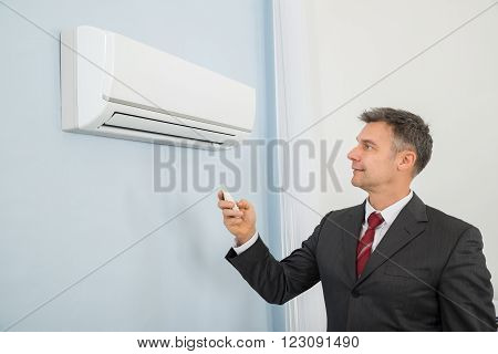 Mature Happy Businessman Using Remote Control To Operate Air Conditioner