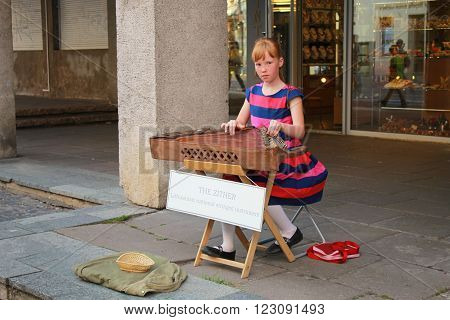 VILNIUS, LITHUANIA - JULY 18, 2015 : Young street musician girl sits on the street and plays on lithuanian national instrument the zither for tourists in Vilnius, Lithuania.