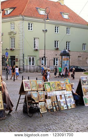 VILNIUS, LITHUANIA - JULY 18, 2015: Street artists sell paintings to the tourists on the street market in Old Town of Vilnius, Lithuania.