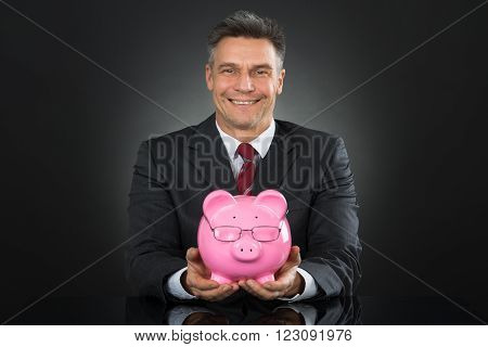 Businessman Sitting And Holding Piggybank