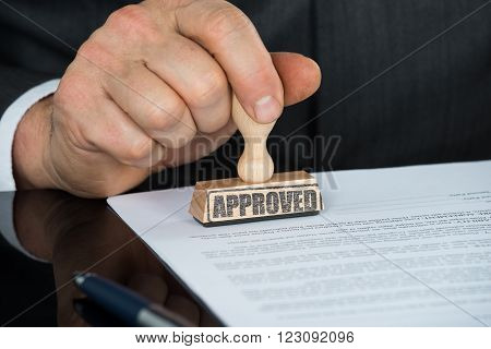 Close-up Of Businessman Hand Stamping On Approved Contract Form