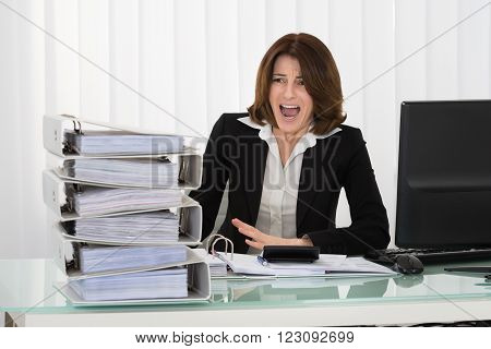 Irritated Businesswoman Looking At Stack Of Folders