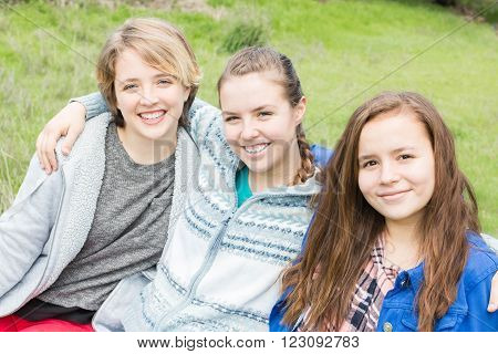 Three Girls Sitting together with green grass in the Background