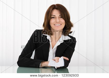 Happy Businesswoman Offering Pay Cheque In Office