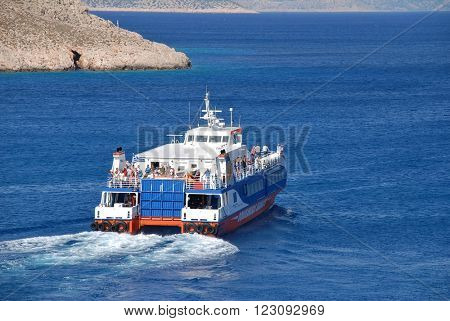 HALKI, GREECE - JUNE 16, 2015: Dodekanisos Seaways catamaran ferry Dodekanisos Express departs Emborio harbour on the Greek island of Halki. The 40mtr vessel was built in 2000 in Norway.