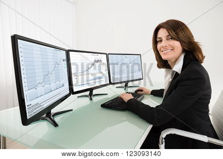 Happy Female Stock Market Broker Working On Multiple Computers In Office