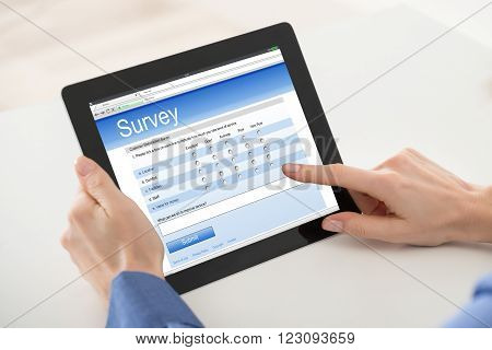 Close-up Of Woman Filling Online Survey Form On Digital Tablet