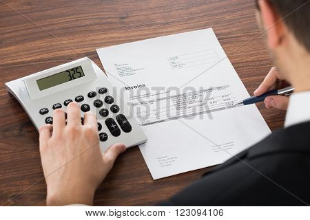 Close-up Photo Of Young Businessman Calculating Bill