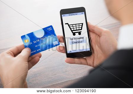 Close-up Of Businessman Paying With Credit Card On Mobile Phone