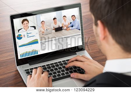 Businessman Video Conferencing With Colleague On Laptop In Office