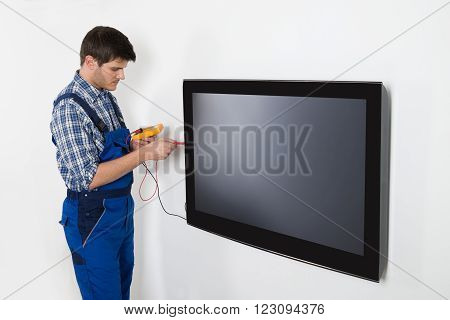 Young Male Technician Repairing Television With Multimeter At Home