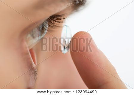 Close-up Of Young Man Putting Contact Lens In Eye