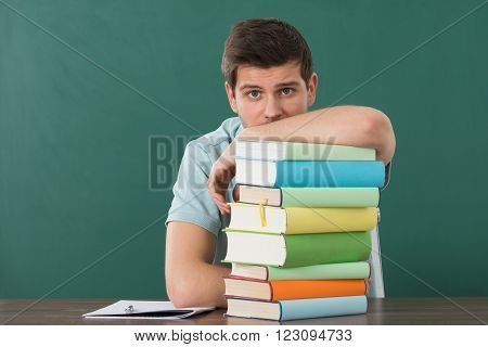 Young Man Leaning On Stack Of Books At Desk