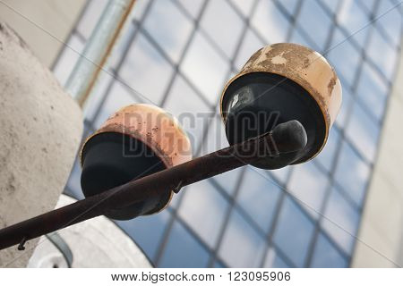 Street warning light rusted with business building behind