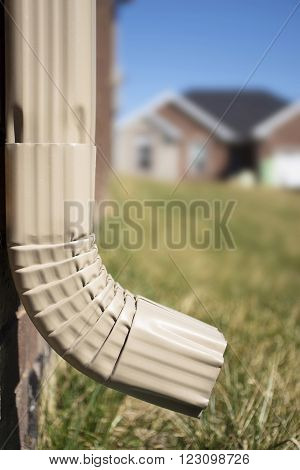 Downspout of a rain gutter showing a house in the background