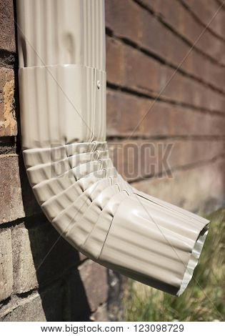 Downspout of a rain gutter showing bricks and grass on the side of a home