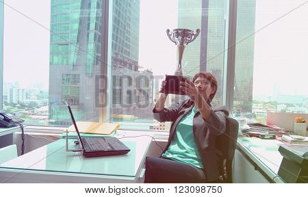 portrait of businesswoman keeping gold cup, office Building  background. Concept of victory and success