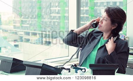 Businesswoman Sitting at her Desk Answering a Telephone Call from a Customer , Vintage Tone