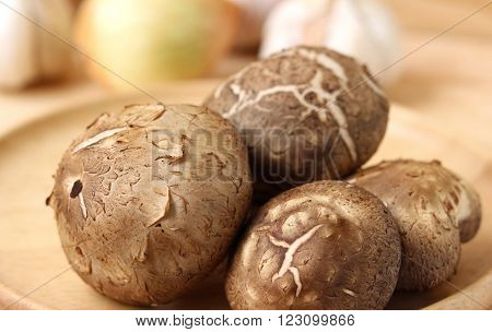 Shiitake mushroom in wooden plate on wooden table