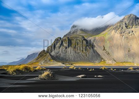 Mountains and black volcanic lava sand dunes by the sea in winter of Stokksness Iceland