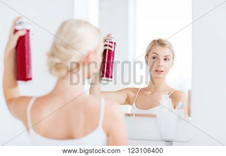 beauty, hygiene, hairstyle, morning and people concept - young woman with hairspray styling her hair and looking to mirror at home bathroom