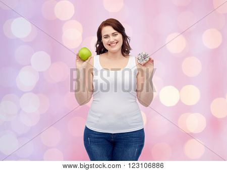 healthy eating, junk food, diet and choice people concept - smiling plus size woman choosing between apple and cookie over pink holidays lights background