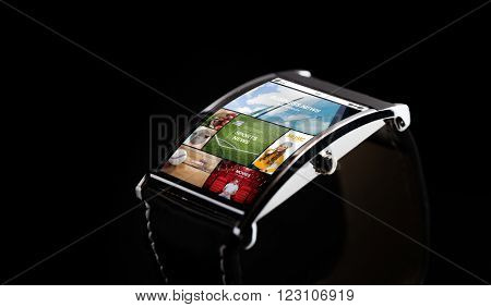 modern technology, mass media, object and media concept - close up of black smart watch with news application on screen