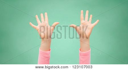 people, childhood, gesture, education and body parts concept - close up of little child hands raised up over green school chalk board background