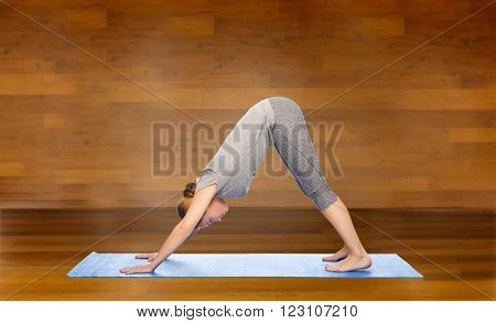 fitness, sport, people and healthy lifestyle concept - woman making yoga in downward facing dog pose on mat over wooden room background