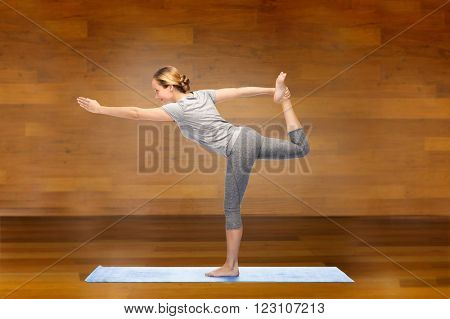 fitness, sport, people and healthy lifestyle concept - woman making yoga in lord of the dance pose on mat over wooden room background