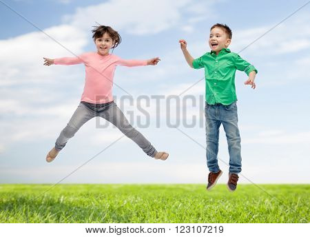 happiness, childhood, freedom, movement and people concept - happy little girl jumping in air over blue sky and grass background