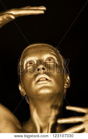 Young beautiful girl in gold looks at his hands