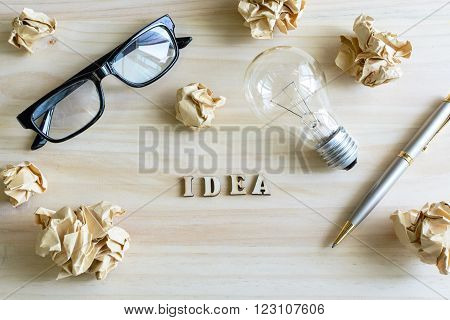 Crumpled paper balls with eye glasses and pen on wooden desk, creative writing concept