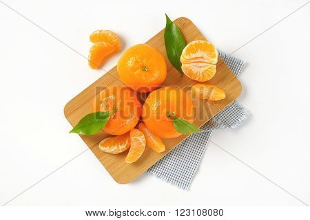 tangerines with separated segments on wooden cutting board