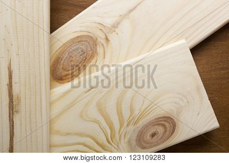 Sawn light wood planks on the wooden background
