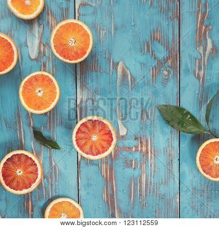 Fresh red oranges. Halved blood oranges with leaves. Top view, vintage toned image, blank space
