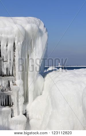 The picture was taken in Ukraine in the area of the port of Odessa. The picture shows a frozen after a strong storm sea water. It seems that this is a fantastic ice architecture. In the background is seen the lighthouse.