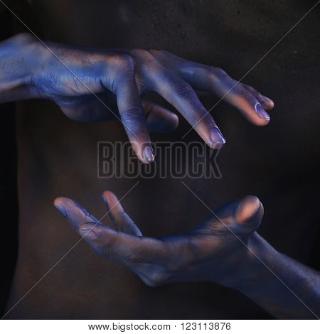 Body Art Tinted Black Man's Hands On The Background Of Male Body
