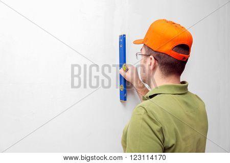 worker man in orange cap using spirit level
