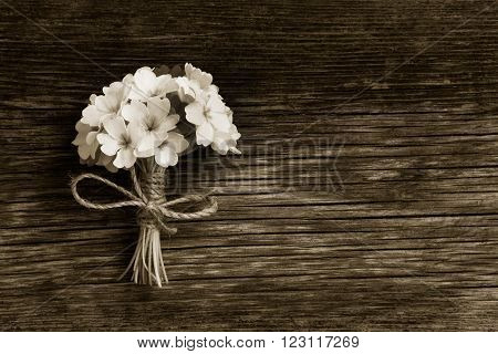 a bunch of primroses tied with string on an old wooden board in the cracks. Free space for text. Copy space. black and white photo