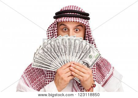 Young Arab hiding his face behind a stack of money isolated on white background