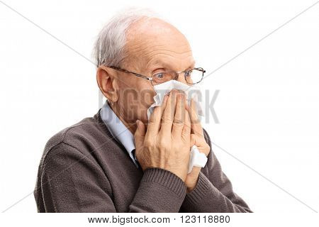 Senior man blowing his nose in a tissue isolated on white background